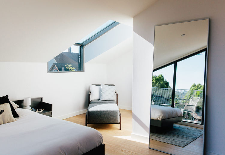 past-perfect-vancouver-multi-family-edwardian-home-renovation-bedroom-spectrum-skyworks-skylight-calligaris-armchair-ottoman-ikea-mirror-bed